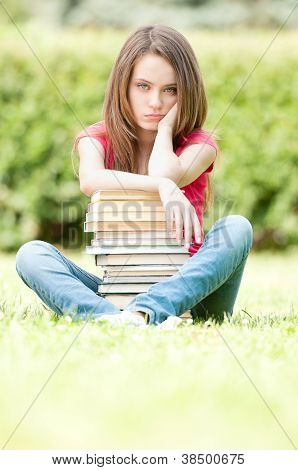 Sad Student Girl Sitting Near Pile Of Books