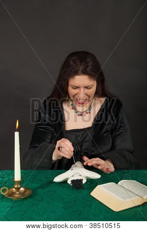 A Dark Dressed Woman Is Stabbing A Doll With A Needle