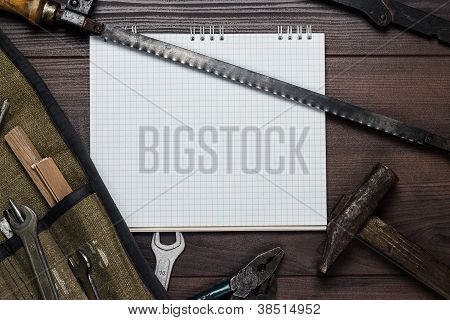 Construction Tools And Blank Notepad On The Wooden Background
