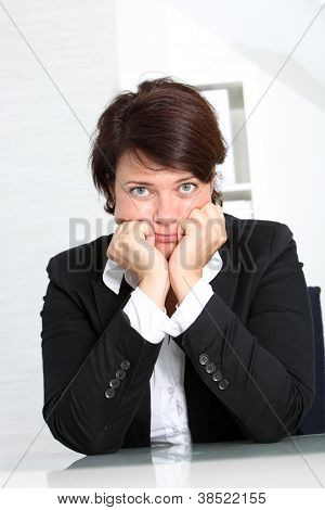 Dejected Businesswoman Seated At Her Desk