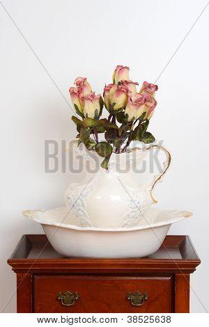 alte Schüssel und Krug auf einem Ständer mit gefälschten Rosen