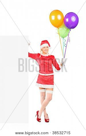 Full length portrait of a sexy female in santa costume holding balloons and standing next to a blank billboard