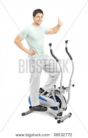 Handsome young man exercising on a cross trainer and giving a thumb up, isolated on white