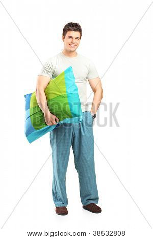 Full length portrait of a smiling man in pajamas holding a pillow isolated on white background
