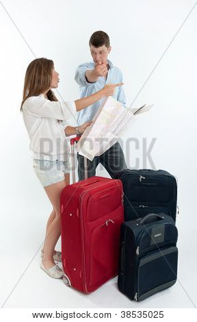 Young couple surrounded by baggage and holding a map angrily pointing to different directions