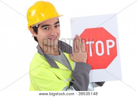 young bricklayer wearing safety jacket and stop sign