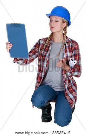 Tradeswoman looking at her clipboard
