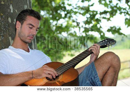 Man playing guitar under tree