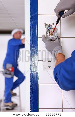 An electrician fixing an outlet.
