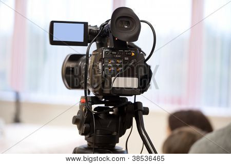 The image of video camera under the tripod