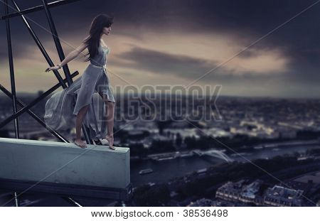 Beautiful woman standing on a cornice