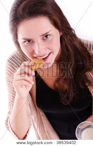 Happy girl eating chocolate cookies with milk at home