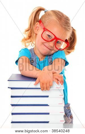 A picture of a young cheerful girl resting her arms on the pile of books against white background