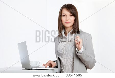 Working on the computer business woman at the office, isolated on white