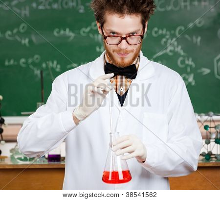 Mad professor hands Erlenmeyer flask with red liquid in his laboratory