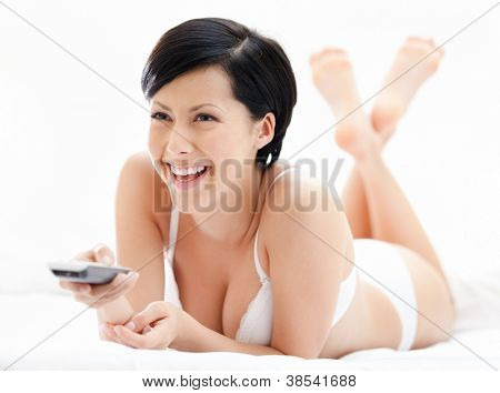 Woman in underwear is lying in the bedstead with handset, isolated on white
