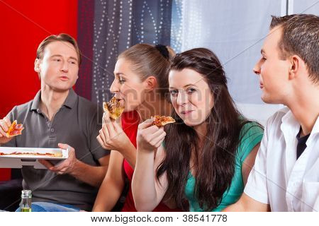Good friends sitting together having a good time and some tasty pizza for lunch, focus on one woman