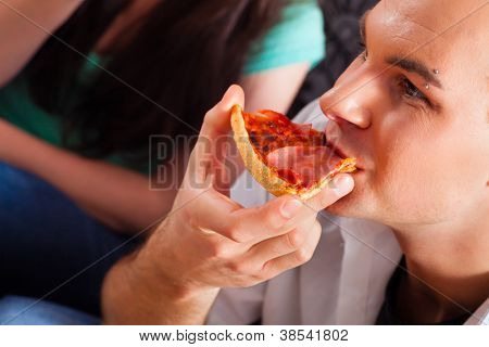 Good friends sitting together having a good time and some tasty pizza for lunch, focus on one man