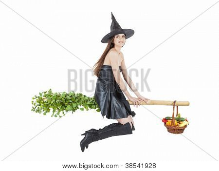 beautiful witch flying on broomstick with vegetable basket