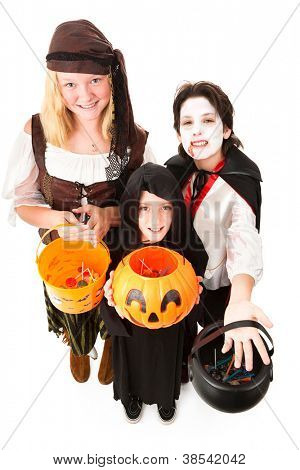 Three children in Halloween costumes, trick or treating.  Full body isolated on white.