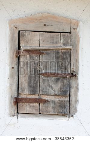Very old shutters on the window is closed on the background of painted clay wall