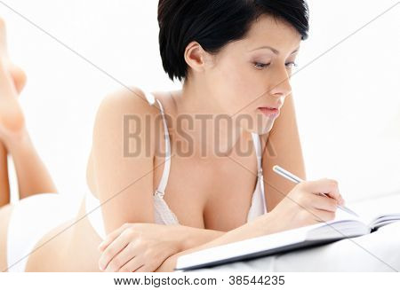 Woman in underwear makes some notes while lying in the bedstead, isolated on white