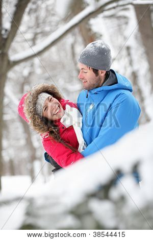 Romantic young couple holding each other in a close embrace and laughing merrily hugging in the snow
