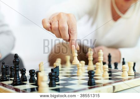 Portrait of senior human hand holding chess figure