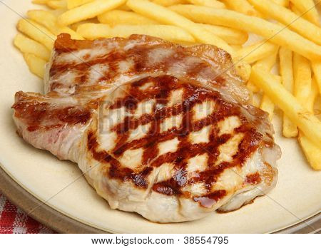 Chargrilled pork steak and fries meal