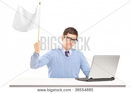 Sad man sitting with laptop and holding a white flag gesturing defeat isolated on white background