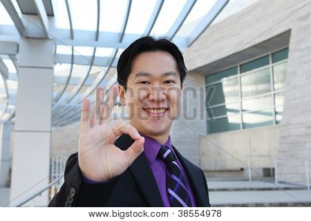 A handsome Chinese business man at office building indicating success