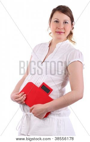 Pregnant woman in white holds red balance isolated on white background.