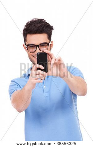 young smiling casual man taking a picture of you with his phone. isolated on white background
