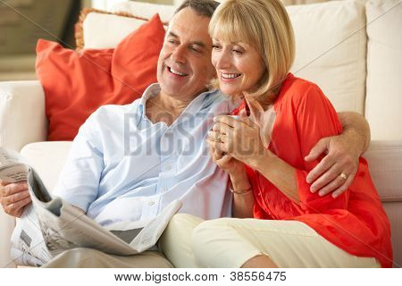 Senior Couple Relaxing On Sofa At Home Reading Newspaper