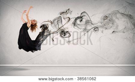 Schöne junge Tänzerin mit schwarzen Rauch Curls um sie herum