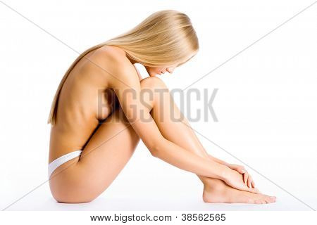 Beautiful half-dressed woman sitting on a white background