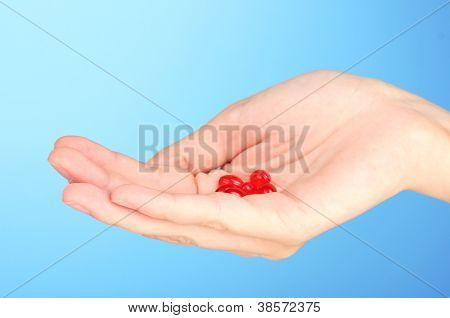 Woman's hand holding a red pill on blue background close-up