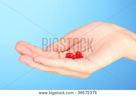 Mano de la mujer una pastilla roja en primer plano de fondo azul