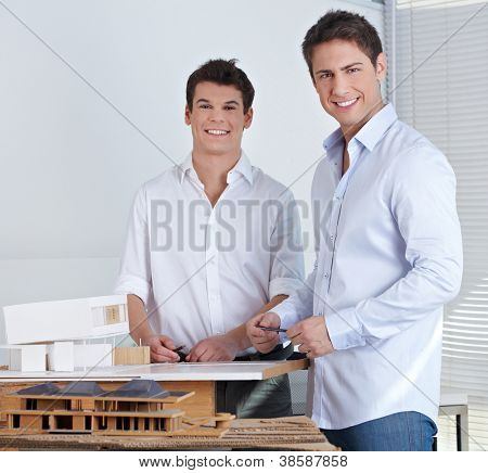 Two happy architects in their office with model of a modern house