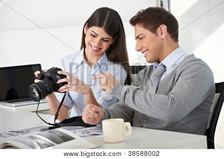 Man and woman sitting with camera in office and looking at photos