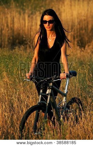 Portrait of pretty young brown haired woman riding a bike - sunset colours