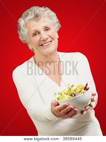 portrait of senior woman showing a fresh salad over red background