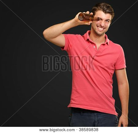 man looking inside an empty bottle isolated on black background
