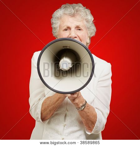portrait of senior woman screaming with megaphone over red background