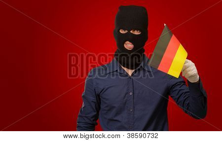 Man wearing robber mask and holding flag on red background