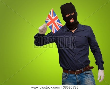 Portrait of a man wearing mask holding a flag isolated on green background