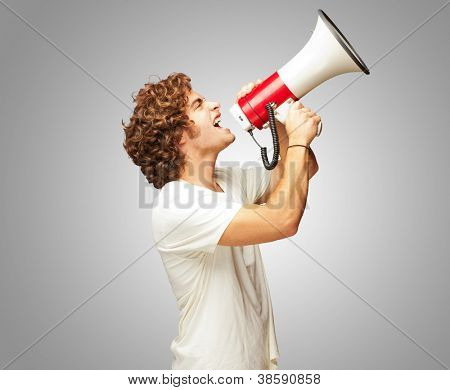 Portrait Of Young Man Shouting With A Megaphone Isolated On Gray Background