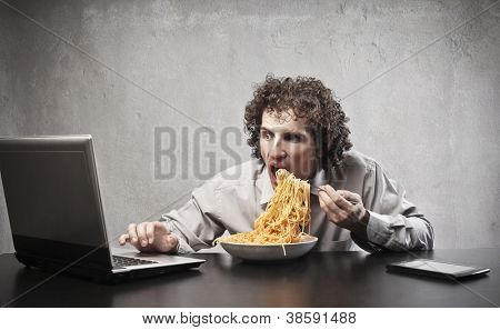 Man gorging of spaghetti with tomato sauce and using a laptop computer