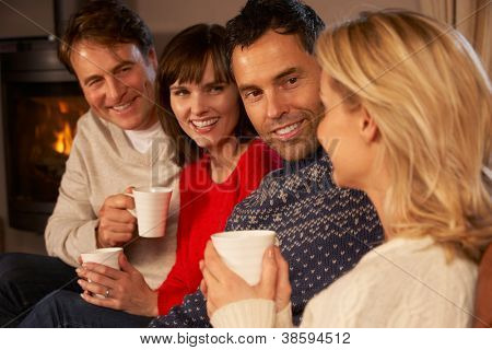 Group Of Middle Aged Couples Sitting On Sofa With Hot Drinks Talking