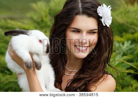 Young woman bride smiling and holding ute rabbit over park summer nature outdoor, Alice in Wonderland
